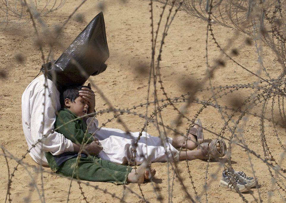 """14. Hərbi əsir qolları arasında  oğluna təskinlik verir. Əl Nəcəf (İraq).  31 mart 2003-cü il. Fotoqraf Jan Mark Buju (Fransa). """"Associated Press"""" agentliyi üçün."""