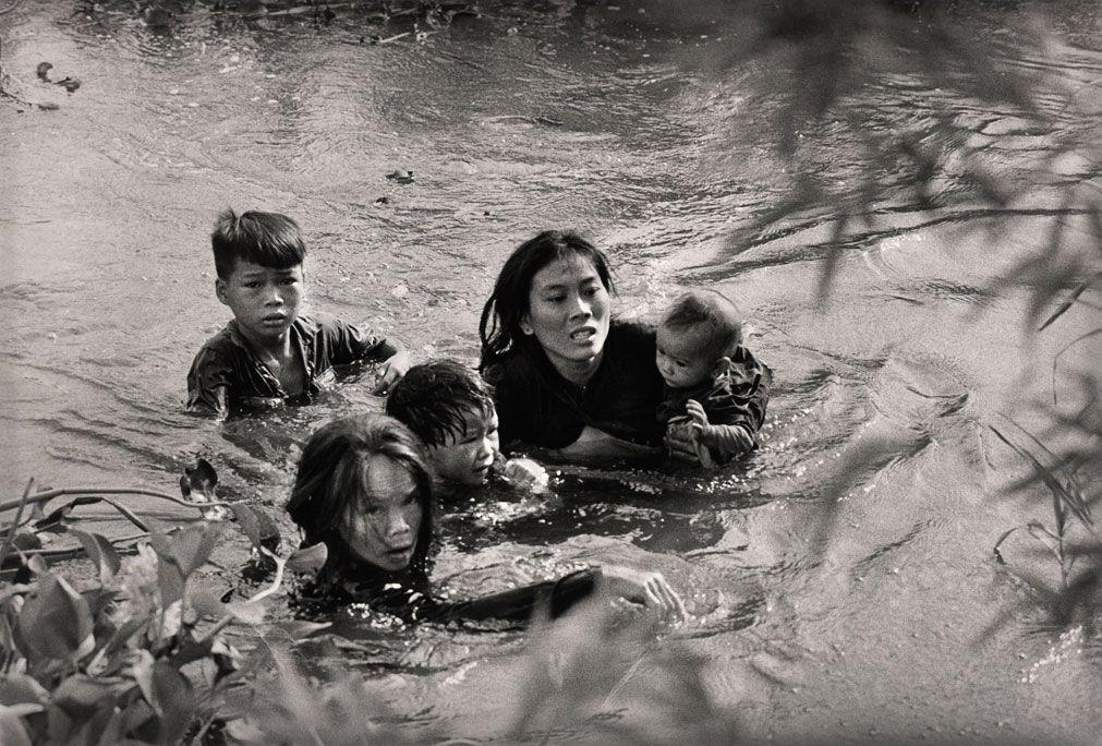 """3. Ana və uşaqları ABŞ ordusunun hava bombardımanından qaçarkən çayı keçir. Sentyabr 1965-ci il. Cənubi Vyetnam. Fotoqraf  Kyoiçi Svada (Yaponya). """"United Press International"""" üçün."""