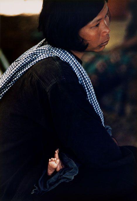 7. Kambocalı məcburi köçkün yemək növbəsini gözləyərkən öz uşağını sakitləşdirir.