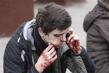 A survivor of a bomb explosion talks on the phone near the exit of Park Kultury metro station in Moscow