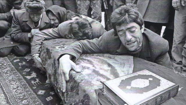 Chingiz Iskenderov, right, weeps over the coffin containing the remains of his brother as other family members grieve in the background at an Aghdam cemetery Thursday. 5 March 1992